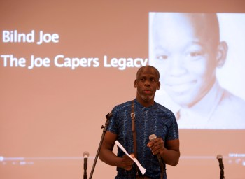 "Image description: Leroy F. Moore, Jr., a Black disabled man giving a lecture. He is standing in front of a microphone and wearing a short-sleeve blue shirt. Behind him on a screen is a slide showing a black and white photo of a young Black child. Left of that photo is text that reads, ""Blind Joe, The Joe Capers Legacy."""