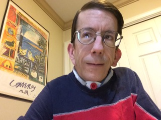 Image description: Portrait photo of a white man, clean shaven, with a tracheostomy, and short brown hair, wearing glasses and a blue and red shirt.