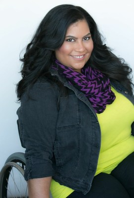 Image description: Danielle Perez sits in her wheelchair. Her long black hair is blown out. Danielle is smiling and wearing a neon green top, with a purple and black stripped scarf, and a black denim jacket.