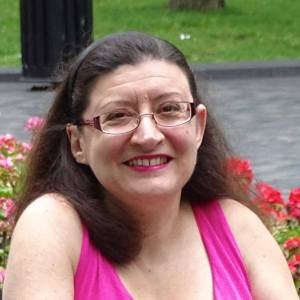 Image description: Caucasian woman with shoulder-length brown hair and glasses is smiling. She is wearing a pink sleeveless dress and is seated in front of a rose bush.