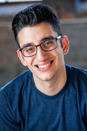 A headshot in which Ryan, a brunette with glasses, wears a navy blue t-shirt and smiles for the camera.