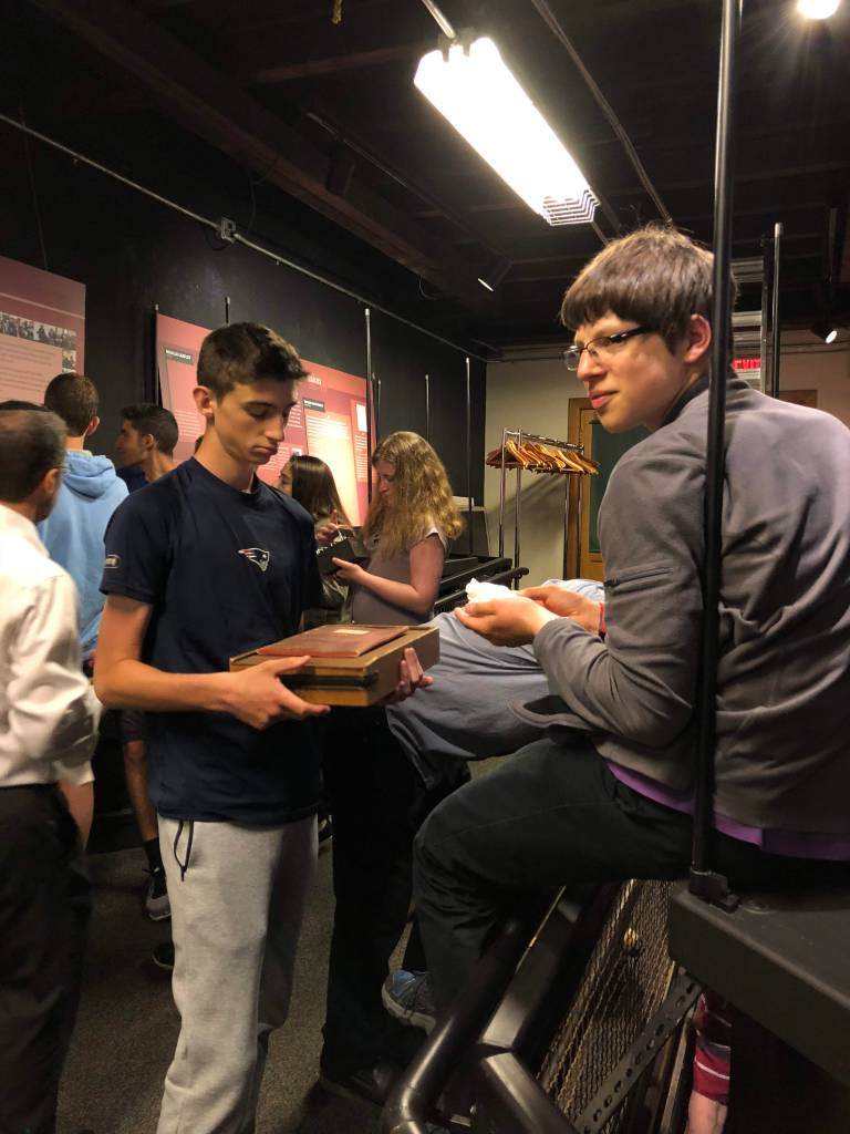 Student Teddy Bennett stands at left in front of an exhibit case holding an early IQ test alongside student Zachary Sherman, putting together a museum exhibit on disability history. Photo courtesy of Gann Academy. Photo credit: Maya Wainhaus