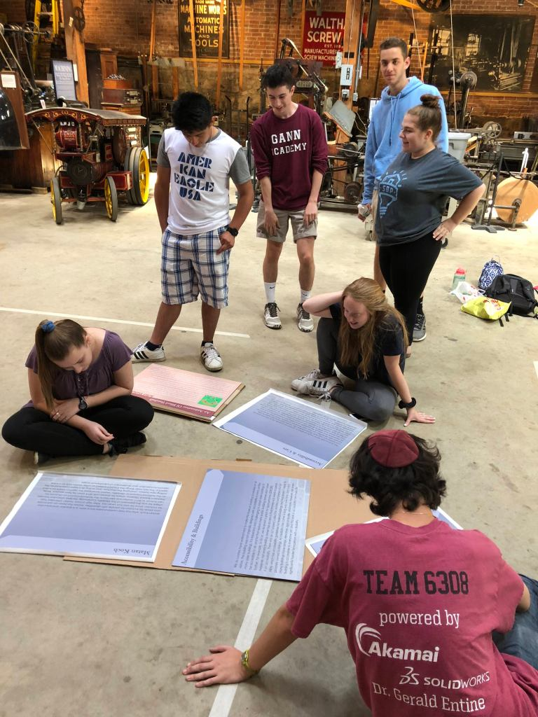 A group of students looking at posters for a museum exhibit that are laying on the ground. Photo courtesy of Gann Academy. Photo credit: Maya Wainhaus