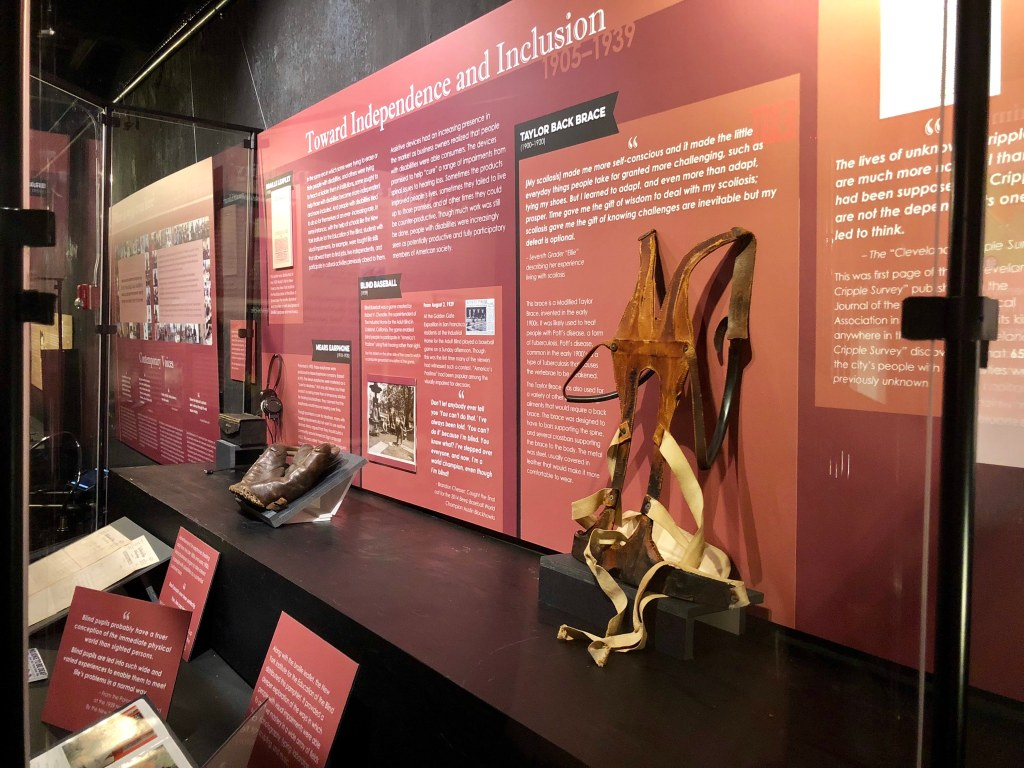 "Disability history exhibit featuring a back brace, a baseball glove, and an early hearing aid. The title for this section: ""Towards Inclusion and Independence 1905-1939."" Photo courtesy of Gann Academy. Photo credit: Maya Wainhaus"