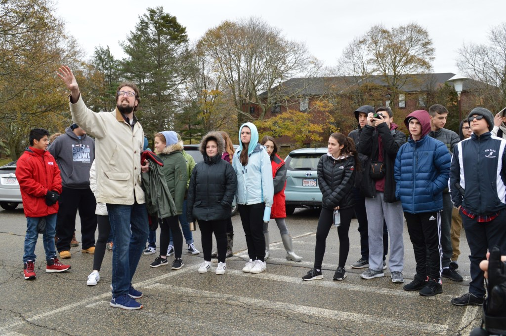 A group of students led by history teacher Alex Green on a field trip to the former Walter E. Fernald Developmental Center. They are standing in a parking lot with Alex pointing toward the Administration Building, which is not pictured. Photo courtesy of Gann Academy. Photo credit: Maya Wainhaus