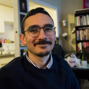 A head and shoulders shot of Angelo, facing the camera and half-smiling. He has short dark hair, a short moustache and goatee, and round metal eyeglasses, and is wearing a navy sweater and striped collared shirt. He is sitting in front of a bookshelf, kitchen, and standing lamp.