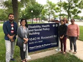 """Outdoor photo with the PRIDE project team in front of a campus sign that reads: """"Disability, Health and Social Policy Building, 1640 W. Roosevelt Rd., Heart Center & Physical Therapy"""" there are large trees in the background."""