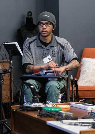 Photo courtesy of Microsoft. A person using an Xbox Adaptive Controller while gaming who appears to be a young man of color in a wheelchair wearing glasses, a gray short-sleeved shirt, green pants, and a gray knit cap.
