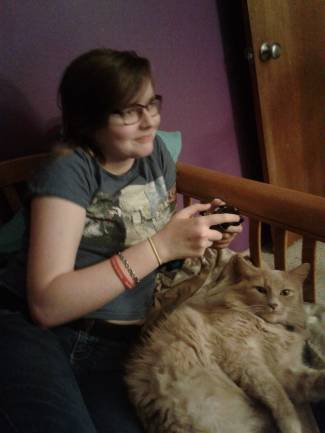 Young white woman with short brown hair and glasses holding a game controller. She is wearing a t-shirt and behind her is a purple wall. A cat is sitting on her lap.