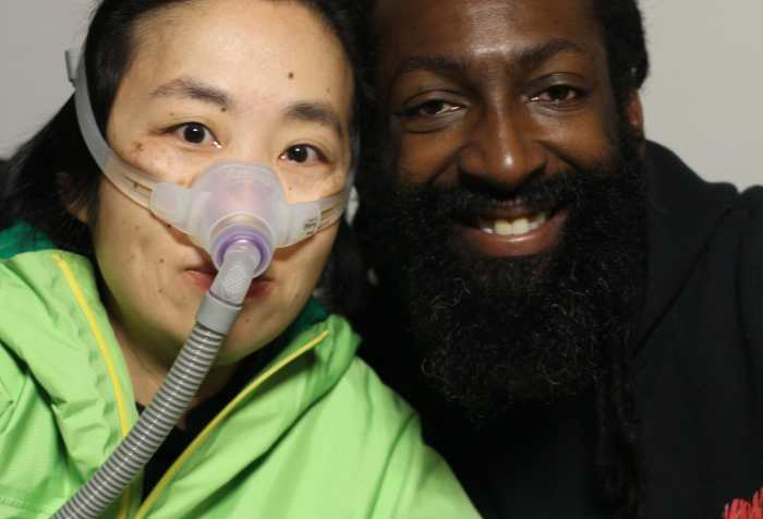 "On the left, Alice Wong an Asian American woman wearing a bright green rain jacket. She is wearing a mask over her nose attached to a gray tube which is connected to her ventilator. She is sitting closely next to Antoine Hunter, a self-described handsome, dark milk chocolate, African American Man. He has long Ebony dreadlocks hair tied to back with a full Ebony-colored beard and full brown lips. He is wearing a black hoodie that says, ""I [heart] Being BLACK."""