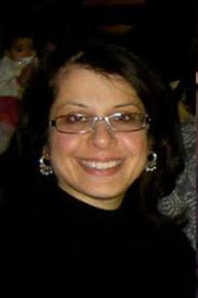 Photo of Dr. Rooshey Hasnain, a South Asian woman with should-length black hair. She is wearing eyeglasses and a black shirt. She is smiling at the camera.