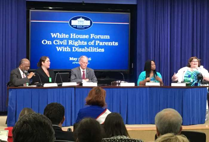 "Five individuals sitting behind a draped table in front of a screen that reads ""White House Forum on Civil Rights of Parents with Disabilities"". At the end of the table is a brunette haired woman sitting in a wheelchair and speaking passionately. Photo courtesy of Rebecca Cokley."