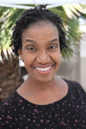 Diana Elizabeth Jordan, a Black woman with short hair in twists smiling at the camera. She is wearing a black scoop neck shirt with a floral print.