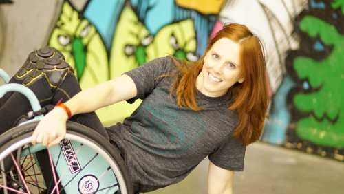 Katherine Beattie, a young white woman with long red hair. She is wearing a gray t-shirt and in her wheelchair popped at a 45 degree angle against a colorful mural.
