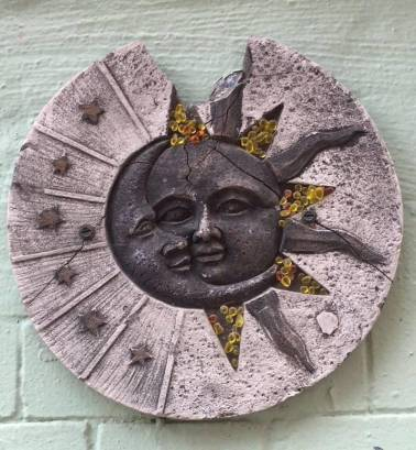 Image of an art piece hung on a lime coloured painted brick will. The image is a gray coloured crescent moon with a face (eyes, nose and mouth) that meets with the sun a circle shaped cement that is chipped at the top creating a crack in the sun Beside the crescent moon on the left are bronze stars. The sun's rays have gold and red pebbles.