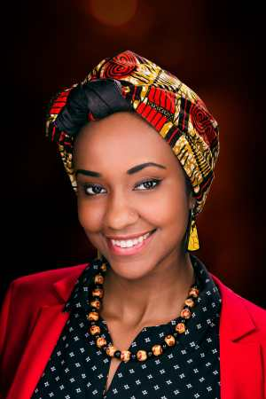Image description by Azza: Azza, a Black woman, wears a bright red and gold hijab with an East African print, red blazer, and black button down blouse. She is smiling at the camera.