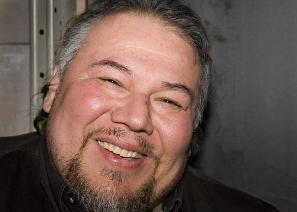 Jeff Thomas, an urban Iroquois man with brown hair with touches of gray and a beard. He is smiling at the camera. Photo credit: Justin Wonnacott