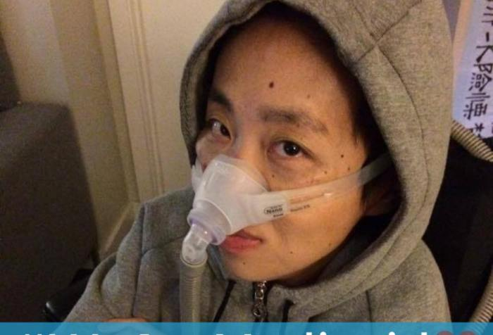 "Image description: Asian American woman wearing a gray hoodie with her hands crossed across her chest. She is sitting in a wheelchair and had a BiPap mask over her nose with a tube. Below is a light blue horizontal bar with white text that reads: ""#WeAreMedicaid."" Next to the text on the right side is a graphic of a pink heart"