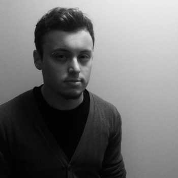 A black and white picture of Dominik, a white man with slightly curly brown hair, a dark pinch, and a piercing over the right eyebrow. He is wearing a cardigan over a black shirt.