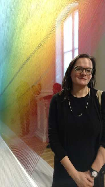Photo of Bess Williamson, a white woman with brown hair and glasses, standing in front of a window and a rainbow thread artwork by Gabriel Dawe.