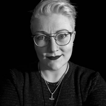 A black-and-white headshot of white person with short platinum blond hair and light eyes. They are wearing a dark grey sweater, round wire-framed eyeglasses, and dark lipstick, and are smiling slightly at the camera.