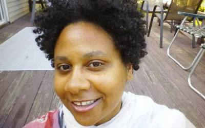 Black woman with curly natural hair wearing a white top with streaks of pink, red, and gray. She is smiling at the camera.