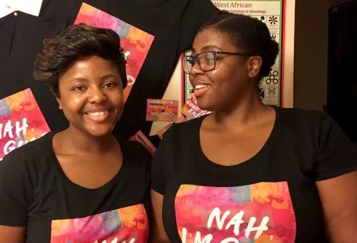 "A picture of two Femmes/Women with almond brown skin and black hair, one with glasses and a ponytail, the other with a short cropped hairstyle. Each of them is wearing a black T-shirt with a colourful slogan saying ""Nah, I'm good love. Enjoy."" In the background, the same T-shirts hang behind them on a cream wall, next to a poster with West African adinkra symbols."