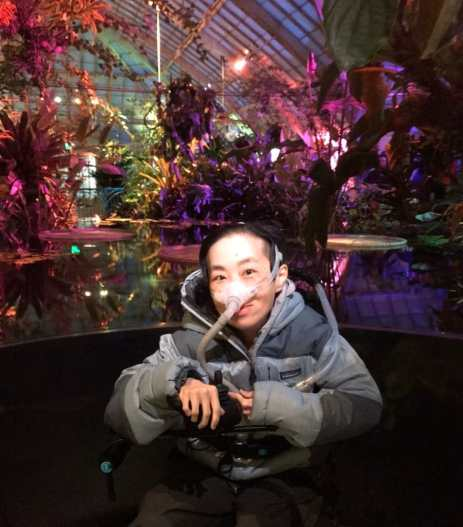 Photo on the of an Asian American disabled woman in a wheelchair in front of a pool of water with tropical water plants in the background lit with purple & magenta lights inside a greenhouse. She is wearing a puffy gray jacket and a mask over her nose attached to a tube.