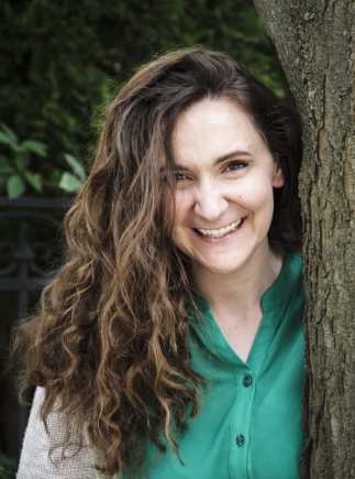 A brown-haired brown-eyed woman stands smiling beside a tree trunk. She wears a deep green shirt and an ivory cardigan.