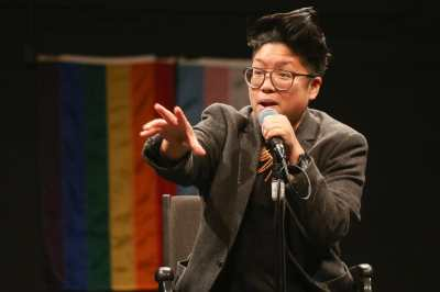 A brown round queer with glasses and short spiky hair performs at a microphone in front of the rainbow and transgender flags. They smile holding a microphone with their hand outstretched.