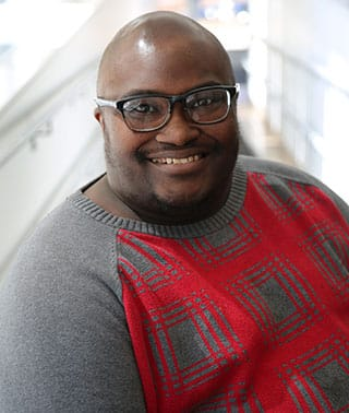 Photo of Finn Gardiner, a bald black man in his 30s wearing glasses and a red and grey sweater.