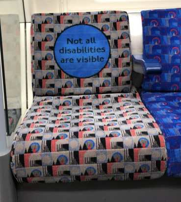 """A picture I took of a London train seat, the back of which says 'Not All Disabilities Are Visible'"""