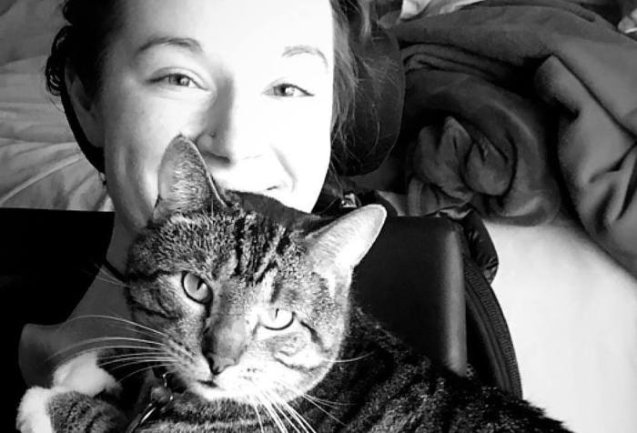 A black and white photo of a light-skinned woman leaning back in her wheelchair, from her shoulders up. Her cat is laying across her chest, looking at the camera. She is smiling.