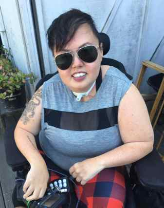 Stacey Milbern Park outside smiling at the camera with gold rimmed aviator sunglasses on. Her short, undercut styled hair is swooped forward over her forehead a little to the right. A tiger tattoo curls up her bare right arm. She is wearing a grey sleeveless tee shirt with a bold black horizontal stripe and red and black plaid leggings.