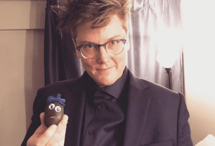 Image is a photo of Hannah Gadsby in a dark suit, holding some of her handmade pet rocks.