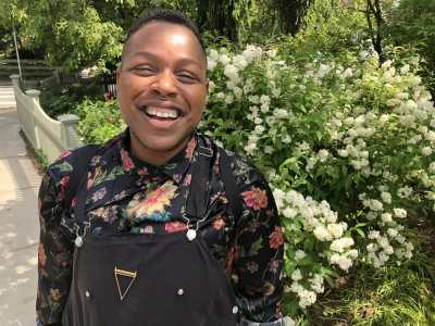 Cyrée Jarelle Johnson, a black transmasculine person with medium brown skin, a septum ring, and a big smile stands in front of a hydrangea bush that is behind a white picket fence on a sunny day. It's so bright his eyes have squinted closed. He is wearing black shortalls, a gold triangle necklace, and a silky, floral black shirt rolled up to the elbows. Photo by J.D. Stokely