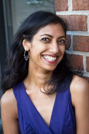This photo is of author Sejal Shah in a sleeveless purple dress in New York City on her old fire escape against the brick background of the building. She is smiling and looking at the camera. Photo credit: Preston Merchant.