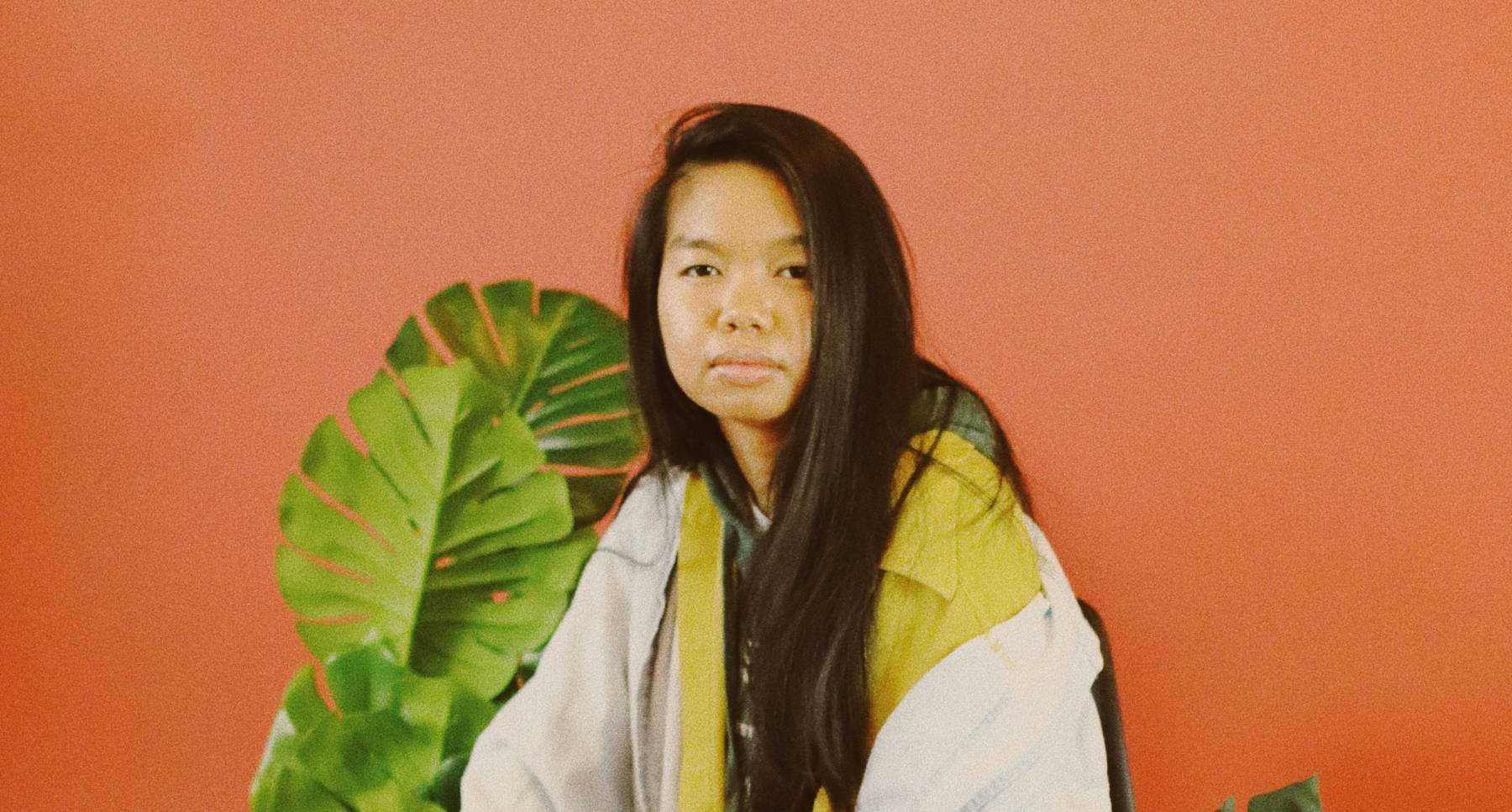 Allison Masangkay (aka DJ Phenohype), a Filipinx femme, sits in a chair wearing an outfit of yellows, greens, lavender, and light wash denim blue with a warm orange backdrop, surrounded by several green plants. They look directly at the camera with a serious expression and their hands resting on their knees. Photo by Bianca Recuenco.