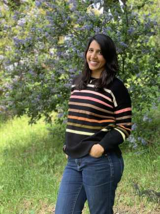 An Indian woman wearing a black sweater with pink and orange stripes and blue jeans smiles in front of a green tree with purple flowers. Her hands are in her pockets.
