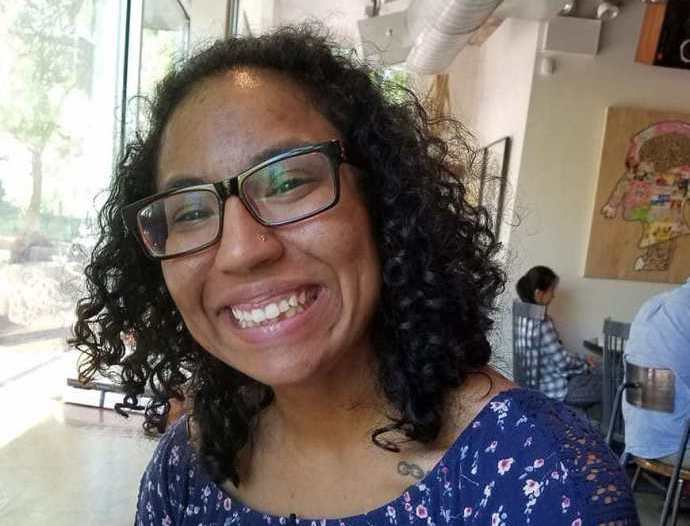 Biracial woman with curly black hair is smiling for the camera. She has black-rimmed glasses and is wearing a blue, flowered romper. She is seated in a coffee shop, backs of patrons visible behind her.