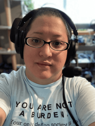 Alejandra is a light-skinned Latina woman with close cropped dark hair. In a close-up selfie, she wears a headset with a microphone, glasses with narrow black frames, and a short-sleeved, light blue shirt where the first part of a quote by Lydia X. Z. Brown is visible: YOU ARE NOT A BURDEN.