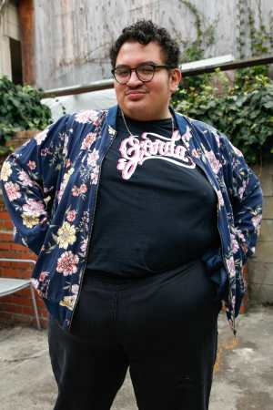 Caleb, a fat brown disabled femme, places their hands on their hips and looks at the camera defiantly. They are wearing blue plants, a blue bomber jacket with pink florals, and a black t-shirt that reads GORDA in a cursive script.