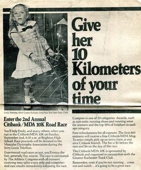 "A black and white newspaper clipping that features an image of a little white girl in a frilly dress surrounded by balloons and looking off into the distance. She is holding onto a metal walker and wearing leg braces. The little girl, Emily Wolinsky, is described in the caption as the ""1984 Greater Rochester Area/New York State Poster Child."" The headline of the clipping states, ""Give her 10 Kilometers of your time,"" and the article discusses a MDA road race for the Muscular Dystrophy Association."