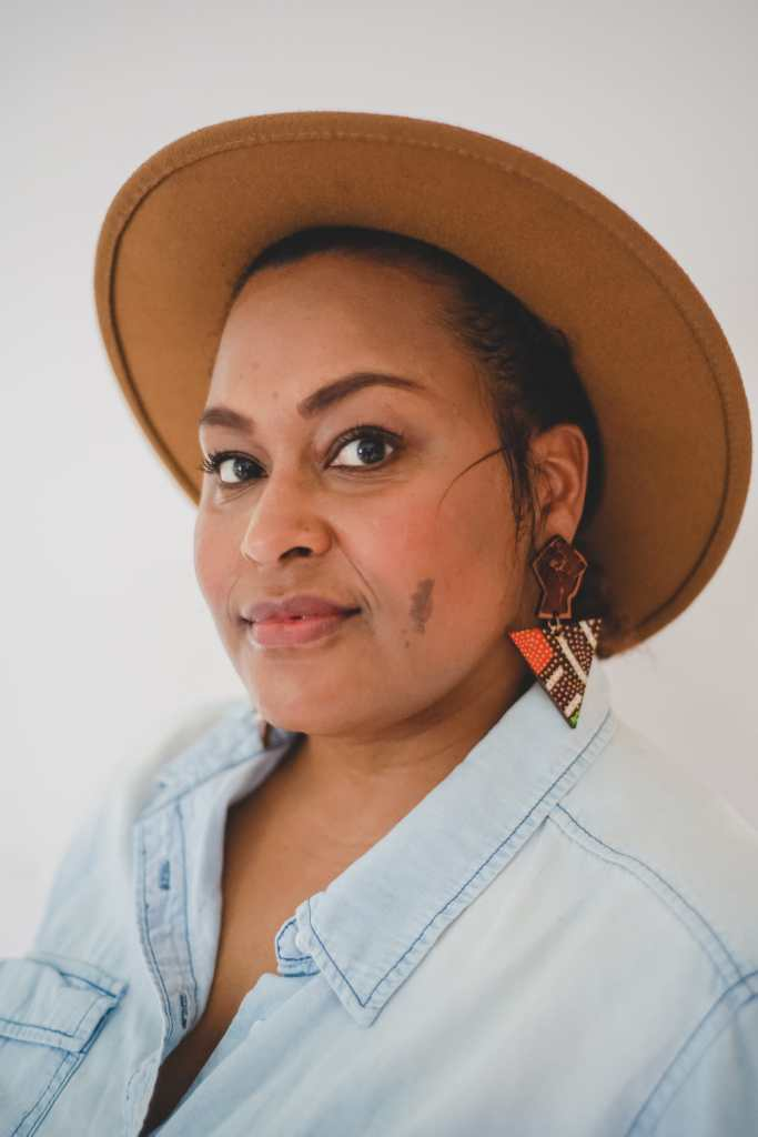 Photo of Jen White-Johnson, an Afro-Latina woman who is wearing a light blue denim shirt. She has a cinnamon complexion with a small brown birthmark on her left cheek. She is wearing earrings with the raised solidarity fist with an inverted triangle below. She is also wearing a wide-brimmed brown hat.
