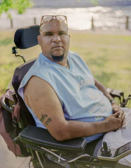 Jay, a Dominican man with a goatee and reading glasses perched on top of his head, sits in a wheelchair outside on a sunny day. There is grass and water in the background. He wears a light blue T-shirt and looks straight into the camera with a serious expression. Photo credit: Elias Williams