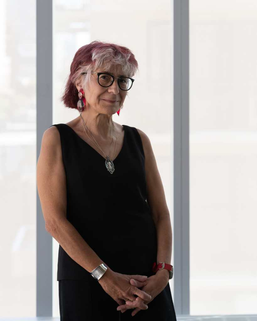 Artist Riva Lehrer, an older white Jewish woman with white hair streaked with red. She is standing against a translucent glass window wearing a sleeveless v-neck black tank and pants. She has a silver necklace, dangly earrings, and glasses on. Her hands are collapsed in front of her torso. Photo credit: Nathan Keay