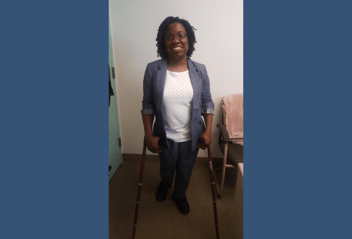 Graphic with a dark blue background with a photo of Britney Wilson, Black woman with curly natural, black hair and glasses in a blue chambray suit and white and blue polka dot top standing on crutches in an office.