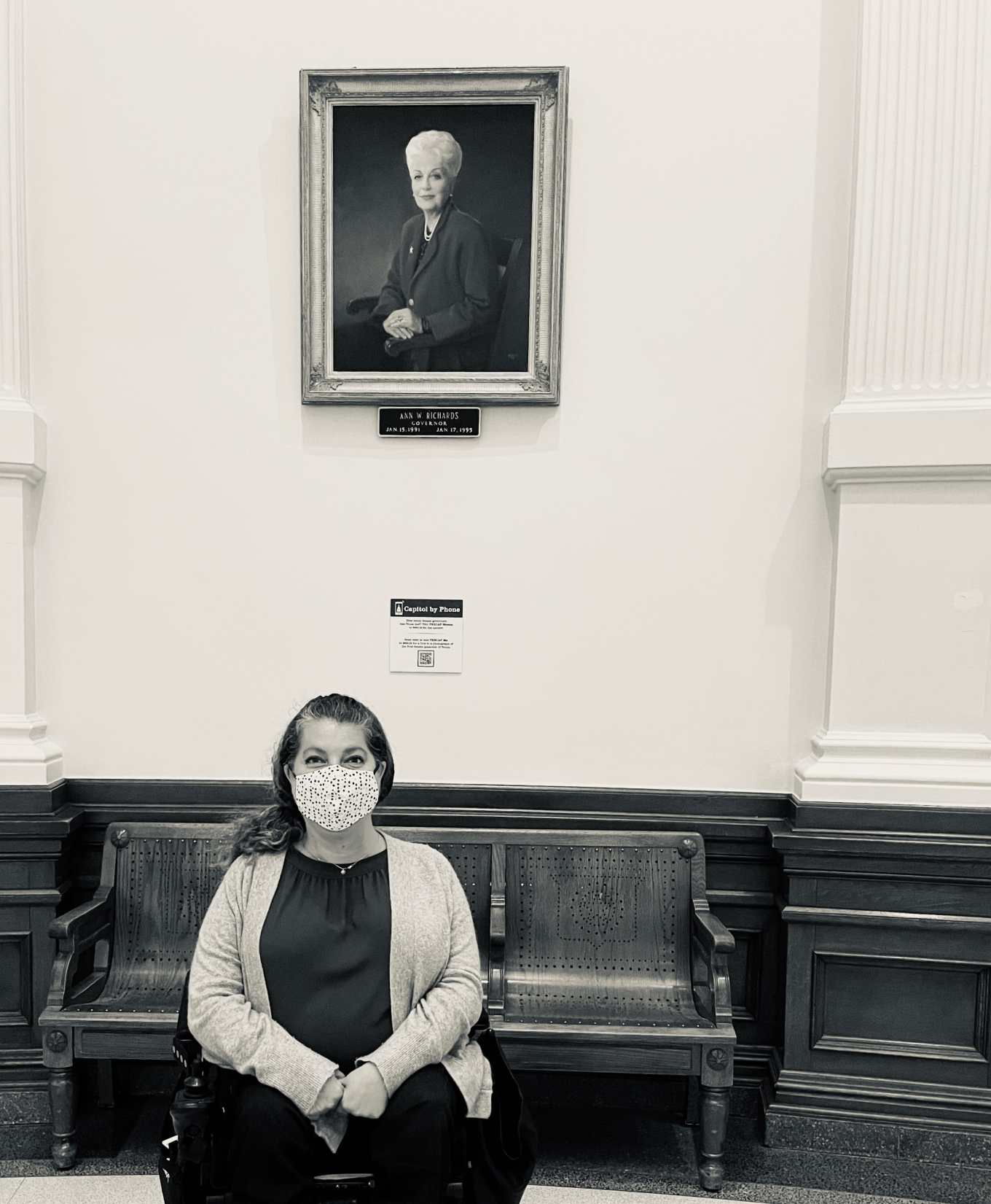 A black and white picture of Emily Wolinsky sitting in her power wheelchair in front of a portrait of the late Governor of Texas, Ann Richards.