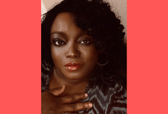 Graphic with a coral background and a head and shoulders picture of Tinu Abayomi-Paul, against a light brown walk. She is a dark skinned woman with chin length curly black hair. She has on red lipstick and her left gold colored hoop earring is visible. She is not smiling, but looks content. She has a hand lightly pressed against her chest and is wearing a dark blue, light blue and black blouse patterned in zigzag stripes. She's looking directly into the camera.