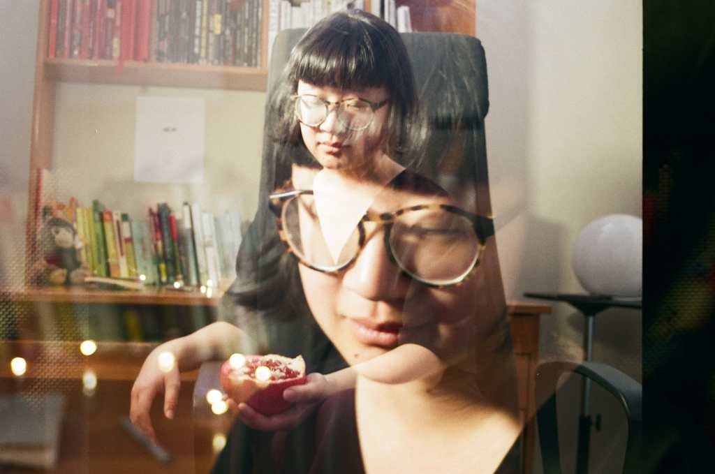 A double exposure photograph, wherein two images are faded onto one another in a single image, of Jane sitting at her desk on a black office chair. Jane is a light skin East Asian person, with her eyes closed, wearing brown and black glasses and short black hair that slightly flares at the end with rounded bangs like a bowl. In one exposure Jane's face is larger and closer to the camera; there are lights directly behind her. In the other, she is sitting on a black office chair and holding a sliced open half of a pomegranate. Behind her is a round, moon-like light. The desk behind her is a medium orange-brown and contains a head shelf, with books ordered in red, black, white, and the rest of the rainbow ordered on the top of the table. There's a small brown monkey plushie near the left end of the desk. There's a black and white ink illustration above the orange to blue books on top of the desk where there's an open space.